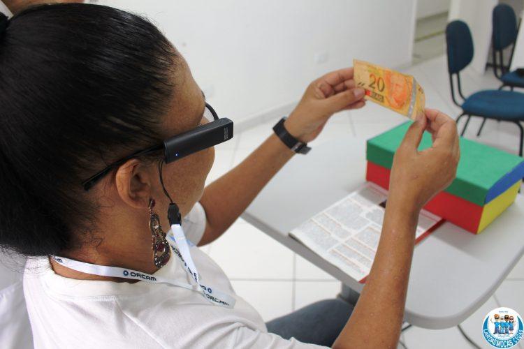 Aluna usando o oculos orcam reconhecendo uma nota de dinheiro