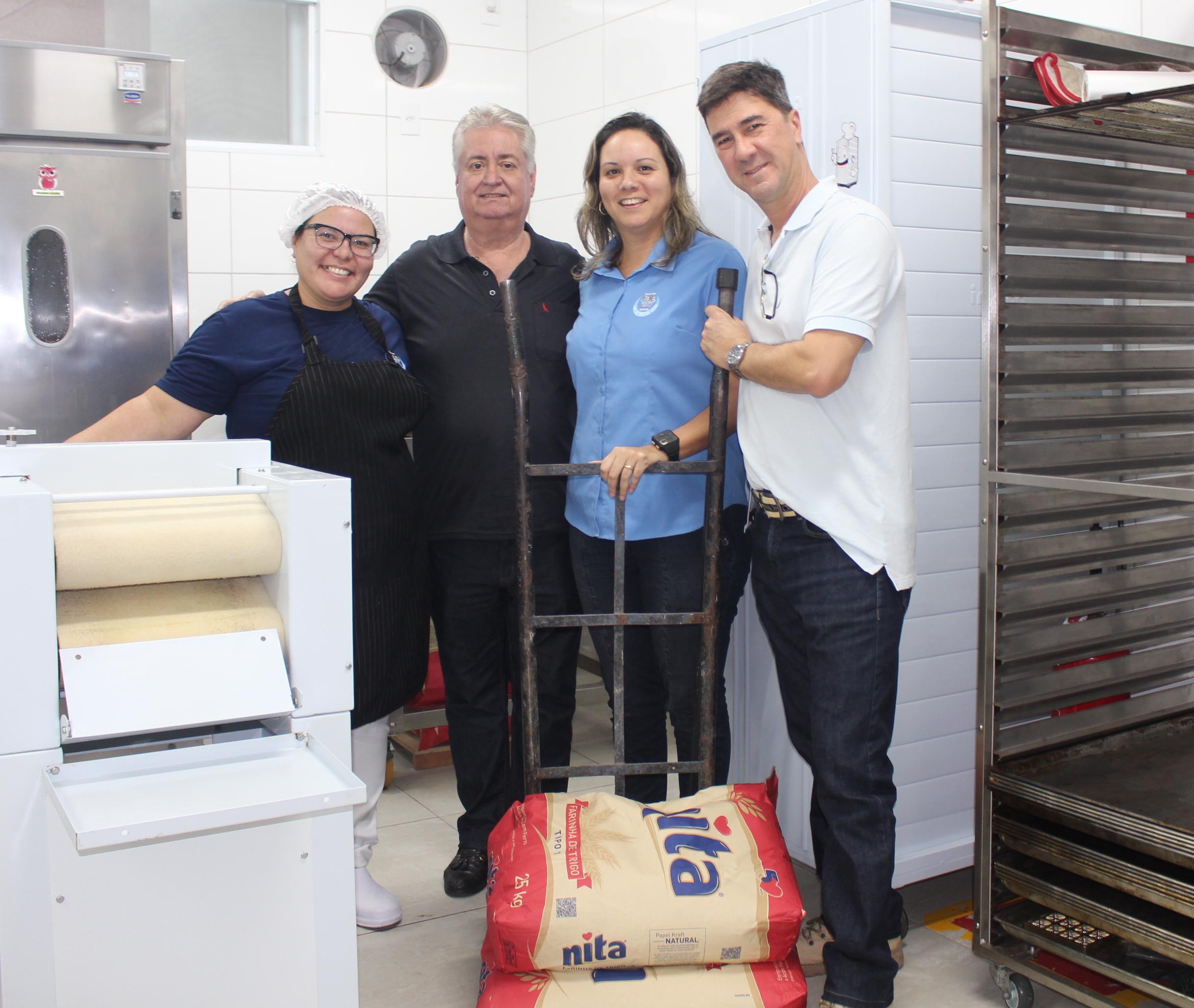 Os amigos Rogério de Oliveira Santos e Márcio Sérgio Teixeira abraçam as professoras Andrea Ferreira e Fabiana Lindinho na doação de farinha para a Padaria Inclusiva do Lar das Moças Cegas.